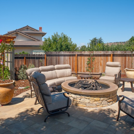 Four beige outdoor furniture seating surrounding a natural stone outdoor fireplace